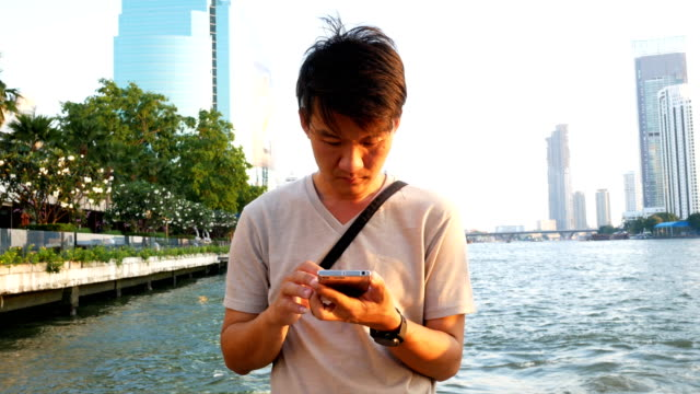 4k asian man using mobile phone outdoor - holing stock videos & royalty-free footage
