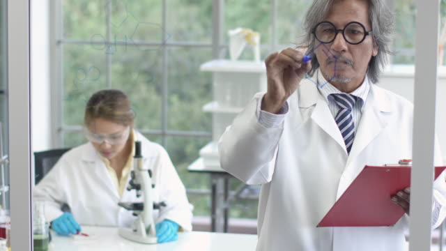 4k: asian scientist writing chemical formula on glass board. - scienza e tecnologia video stock e b–roll
