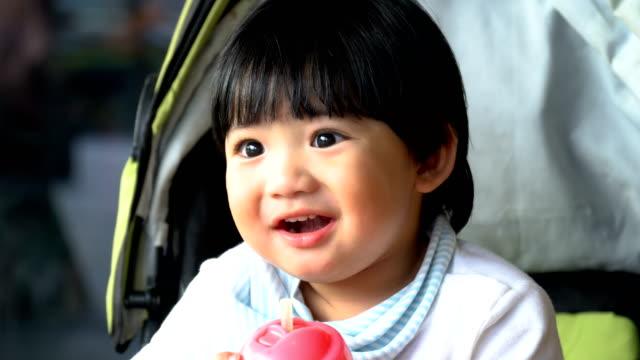 4k cu asian toddler drink juice via straw - pushchair stock videos & royalty-free footage