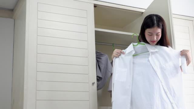 vídeos de stock e filmes b-roll de 4k; asian woman choosing and trying shirt from closet. - closet