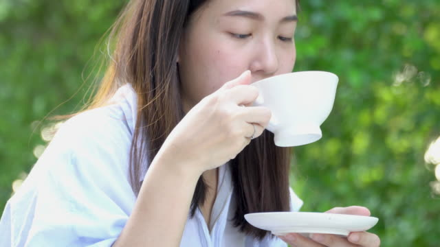 4k; asian woman drinking some hot drink in balcony at the morning. - veranda stock videos & royalty-free footage