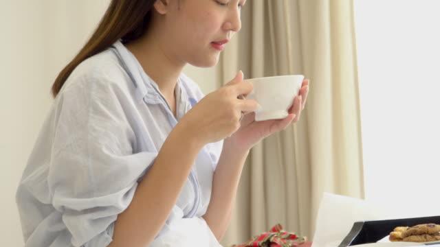 4 k;アジアの女性の寝室で朝のいくつかの飲み物を飲んでします。 - カップ点の映像素材/bロール