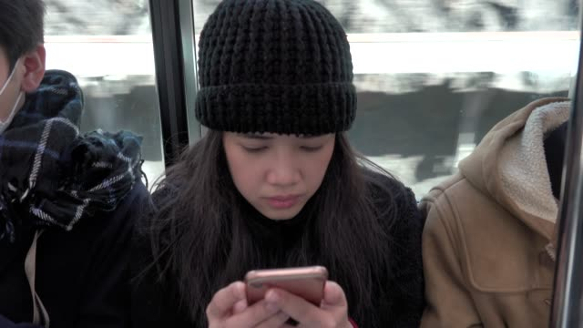 4k: Asian woman in the mass public transportation using her phone while sitting