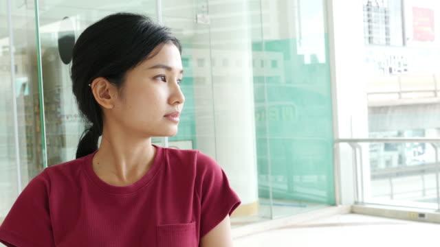 vidéos et rushes de 4 k : asiatique femme regardant à l'extérieur - nostalgie