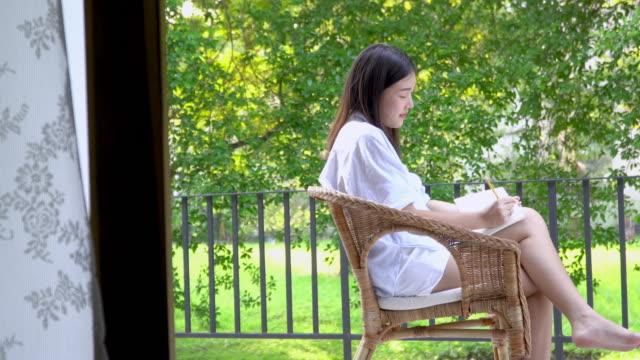 4k; asian women writing and thinking something at balcony. - veranda stock videos & royalty-free footage