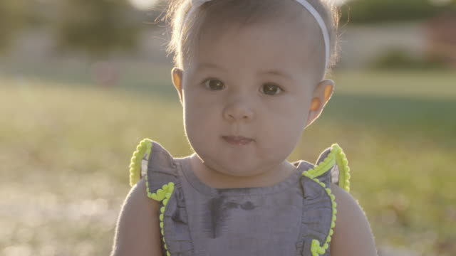 stockvideo's en b-roll-footage met 4k baby girl staring at camera. - haarband