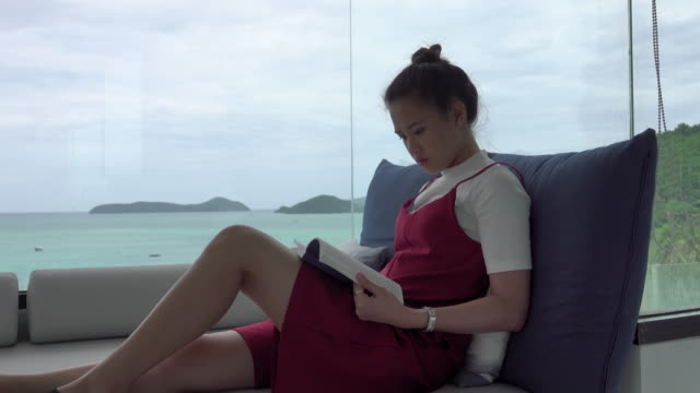 4k: beautiful asian women reading a book with ocean background - schoolgirl stock videos and b-roll footage