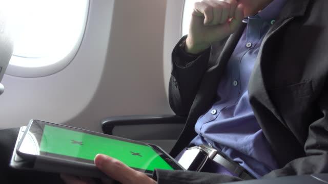 4k: asiatische geschäftsmann mit tablet auf das flugzeug mit greenscreen - flugpassagier stock-videos und b-roll-filmmaterial
