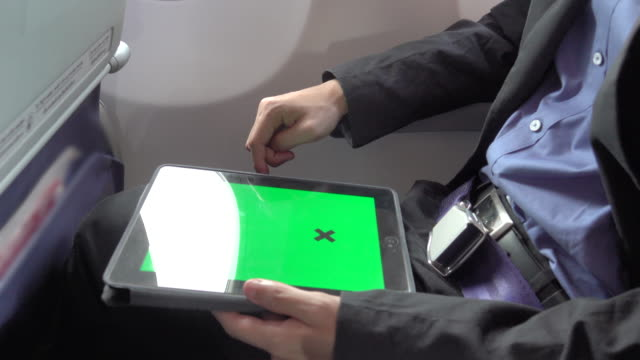 4k: business Asian man using tablet on the plane with green screen