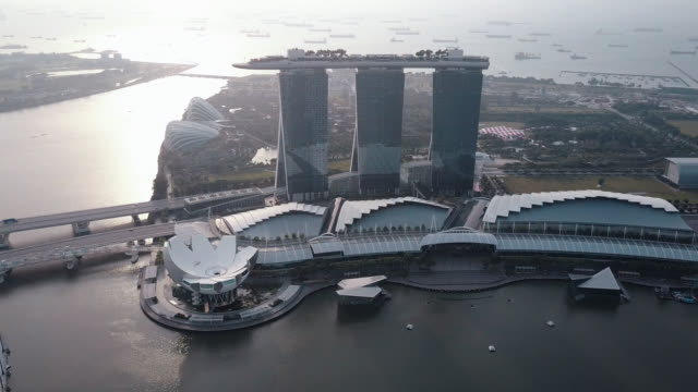 vidéos et rushes de 4k cinematic b-roll footage. view of a flying drone above singapore skyline surrounding marina bay area during sunrise - singapour