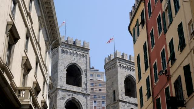 4k clip of the porta soprana castle wall and towers of the city of genoa. shot in summer capturing warm tones and flags flying in the breeze. - monumento video stock e b–roll