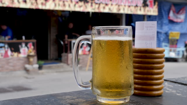 4k close up of chilled cold beer and bill in hot summer weather in the tourist resort bar of pattaya thailand. - beer glass stock videos & royalty-free footage