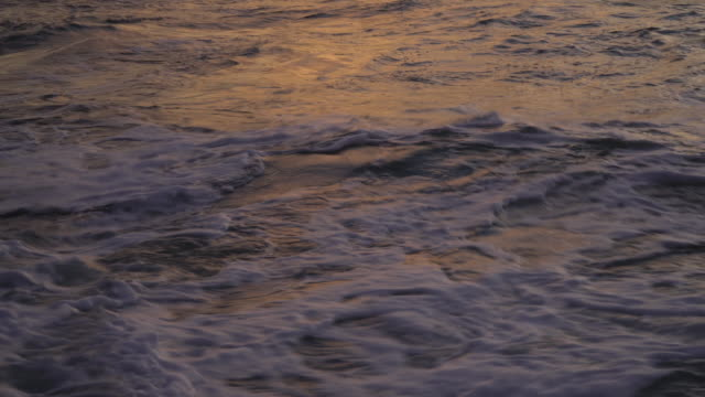 4k close up of textured background sea wave at sunset. - rhythm stock videos and b-roll footage