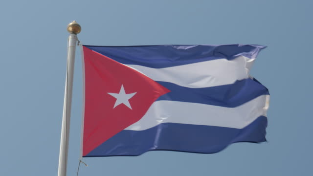 4k close up slow motion of cuba national flag flying proudly in the wind on a warm beautiful bright summer day. - fahnenstange stock-videos und b-roll-filmmaterial