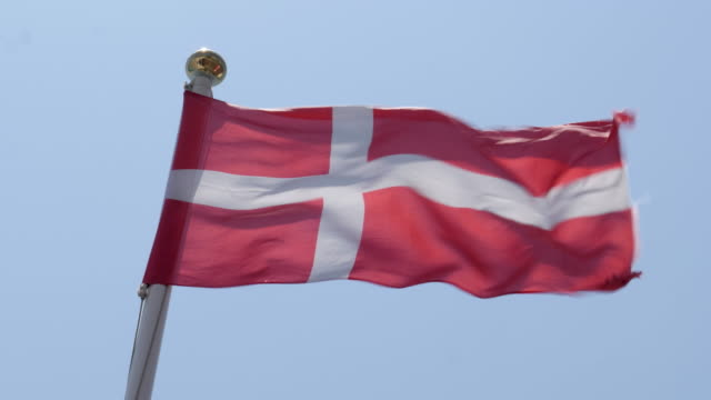 vídeos de stock e filmes b-roll de 4k close up slow motion of denmark flag flying proudly in the wind on a warm beautiful bright summer day. - região de oresund