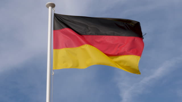 4k close up slow motion of german national flag flying proudly in the wind on a warm beautiful bright summer day. - german flag stock videos & royalty-free footage