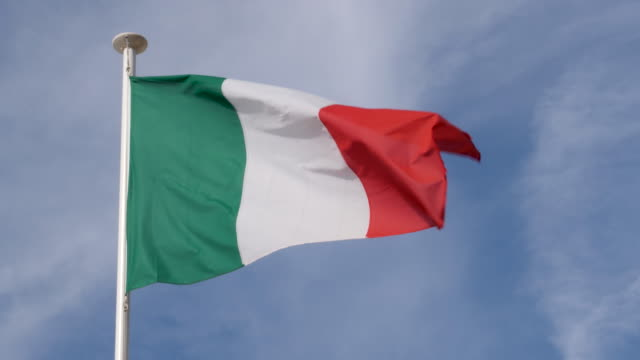 4k close up slow motion of italy flag flying proudly in the wind on a warm beautiful bright summer day. - italienische flagge stock-videos und b-roll-filmmaterial