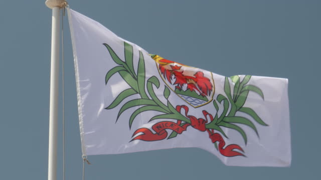 4k close up slow motion of nice city flag flying proudly in the wind on a warm beautiful bright summer day. - fahnenstange stock-videos und b-roll-filmmaterial