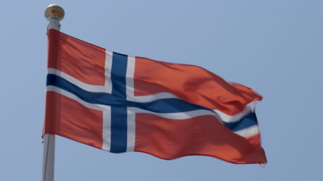 4k close up slow motion of norway national flag flying proudly in the wind on a warm beautiful bright summer day. - fahnenstange stock-videos und b-roll-filmmaterial