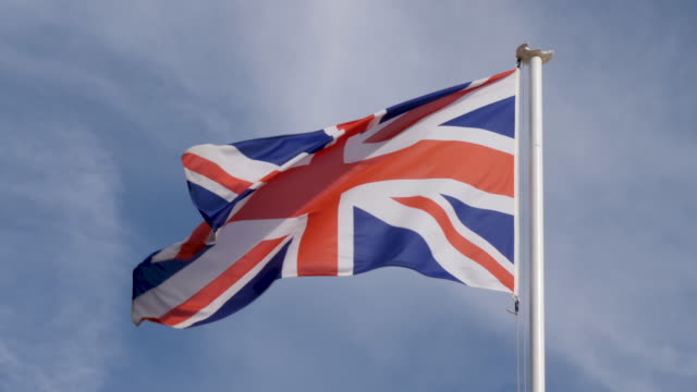 stockvideo's en b-roll-footage met 4k close up slow motion of united kingdom union jack flag flying proudly in the wind on a warm beautiful bright summer day. - geïsoleerde kleur