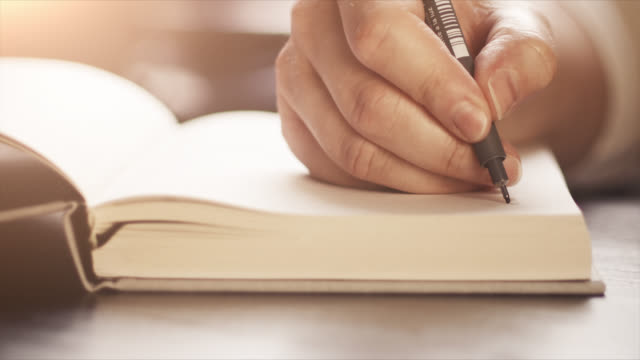 4k close-up of a hand writing in a notebook - slow motion - handwriting - alfabeto video stock e b–roll