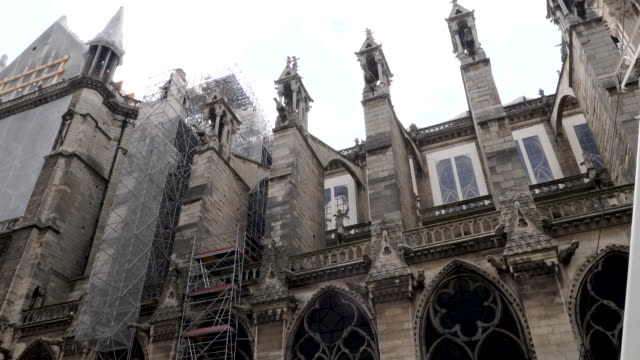 4k construction repair restoration of cathédrale notre-dame de paris severely damaged by fire. towering, 13th-century cathedral with flying buttresses & gargoyles. - notre dame de paris stock videos & royalty-free footage
