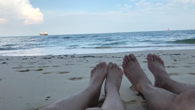 stockvideo's en b-roll-footage met 4k: paar zitten op strand focus alleen voet - menselijke ledematen
