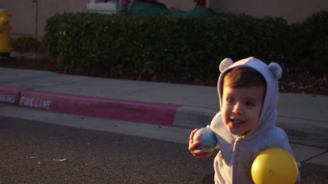 4k Cutest little boy in a bear costume playing with Ball