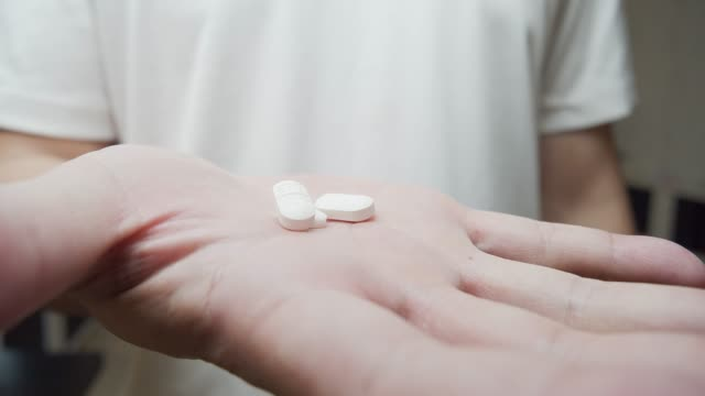 4k dci footage of closed up  shot man hand holding a white medicine pill - taking medicine stock videos and b-roll footage