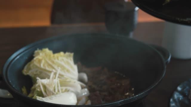 4k dci footage of japanese cuisine, sukiyaki beef ,spring onion stirred and fried on a pan - sukiyaki stock videos and b-roll footage
