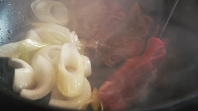vídeos de stock e filmes b-roll de 4k dci footage of japanese cuisine, sukiyaki beef ,spring onion stirred and fried on a pan - vapor