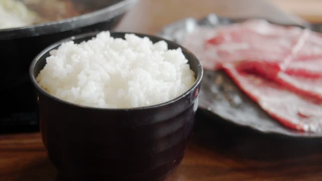 4k dci footage of japanese rice and slice of beef for making a sukiyaki - rice stock videos & royalty-free footage