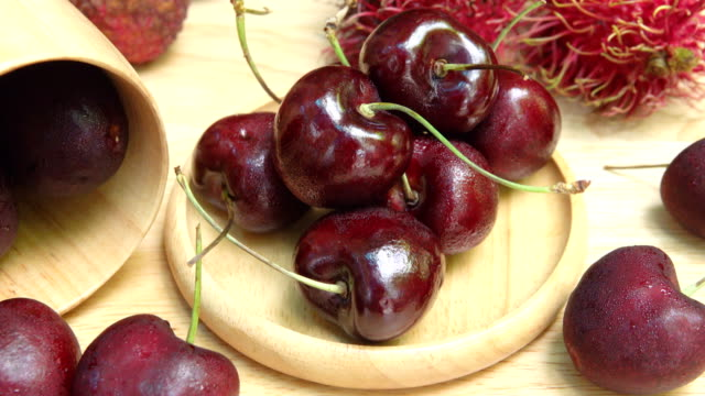 4k dolly shot: cherries on wooden table