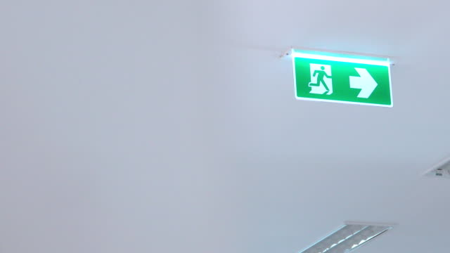 4k Dolly shot: Green emergency, fire exit sign