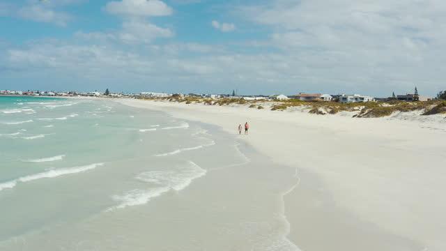 stockvideo's en b-roll-footage met 4k dronebeelden van een stel dat een ontspannende wandeling langs een strand maakt - sunny