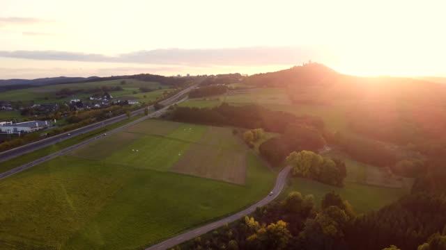 4k beschossen drohne road trip und natur nurburg sonnenuntergang, deutschland. - flugzeugperspektive stock-videos und b-roll-filmmaterial