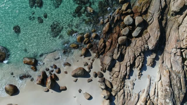 4k drone pov touquoise water golden rocks on sandy beach waves - wilderness stock videos & royalty-free footage