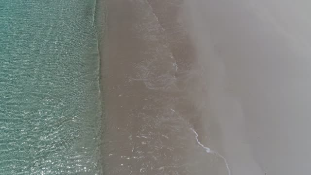 4k drone vertical pov waves breaking gently on golden beach
