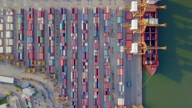 stockvideo's en b-roll-footage met 4 k drone weergave vliegen boven internationale haven met kraan laden van containers in de import export bedrijf logistiek. - ketting