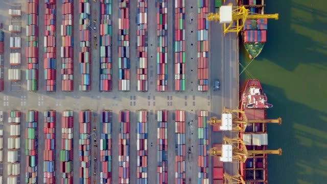 4k drone view flying above international port with crane loading containers in import export business logistics. - chain stock videos & royalty-free footage