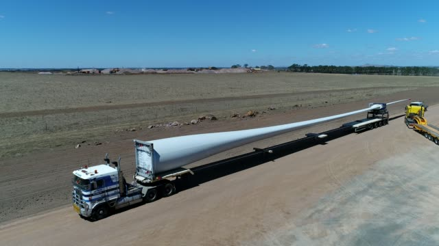 vídeos y material grabado en eventos de stock de 4k drone wind farm and blades on truck - sobreexpuesto