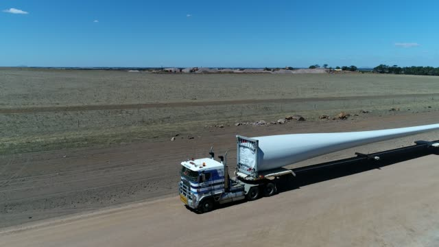 4k drone wind farm and blades on truck - mill stock videos & royalty-free footage