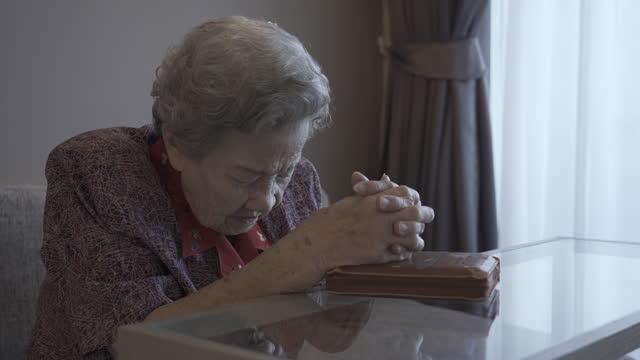 4k : elderly woman praying at home - 70 79 years stock videos & royalty-free footage