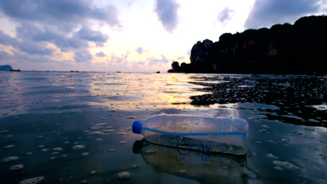 4k: environmental pollution, bottle on the sea in sunset - rubbish stock videos & royalty-free footage