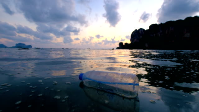 4k: environmental pollution, bottle on the sea in sunset - bottiglia video stock e b–roll
