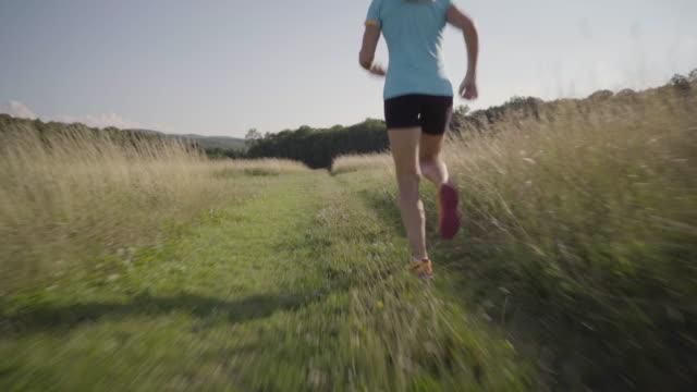 4k following woman jogging outdoors in grassland