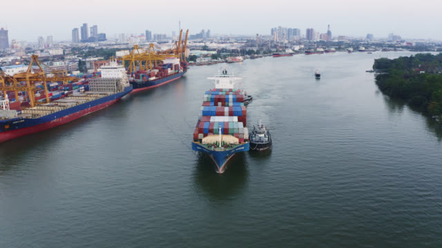4k footage aerial view of drone flying above international port with working crane at sunset in Bangkok Thailand