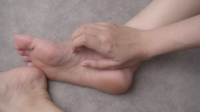 4k footage close up shot asian woman scratching on her feet at home. healthcare and medical concept - scratching stock videos & royalty-free footage