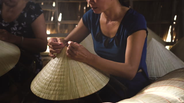 4k footage low light scene closeup of vietnamese craftsman making the traditional vietnam hat in the old traditional house in ap thoi phuoc village, cantho province, vietnam, traditional artist concept - craft stock videos & royalty-free footage