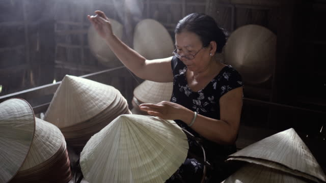 4k footage low light scene of Old Vietnamese craftsman making the traditional vietnam hat in the old traditional house in Ap Thoi Phuoc village, Cantho province, Vietnam, Traditional artist concept